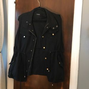 Black sleeveless utility jacket with gold buttons